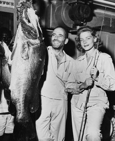 """""""On the left is an 80-pound perch caught in Lake Albert in British Yganda. In the center, proud, happy and beaming over the catch, is me. On the right is the dame who caught it."""" Humphrey Bogart"""