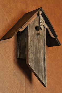 This birdhouse is made from reclaimed barn wood from the Pacific Northwest. Its natural aged finish has been preserved. An acorn and two handmade feathers adorn the roofline of the birdhouse. This birdhouse is quite durable therefore it is suited for either use inside or outside