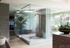 Designer Lynda Murray and architect Chad Oppenheim fashioned a spa-like retreat for the bathroom of filmmaker Michael Bay's Miami home. Etched-stone tiles sheathe a wall that separates two distinct bathing areas; the shower fittings and sink are by Boffi, the countertops are of Macassar ebony, and the cast-concrete tub is a custom design.