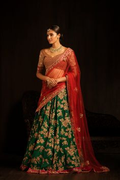 Classical bridal contrast with this dark green bias cut lehenga, sprayed with floral peeta embroidery all over, is teamed with a plum red cholee with fine marodi embroidery all over, done in antique tones. The look Is completed by a red tulle dupatta edged with a marodi border. #bridal #trends #bridal2017 #bridalfashion #bridaldress #weddinglehenga