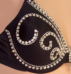 Black Maidenform underwire bra to fit 32A. The cups of the bra are soft but strong. The bra has standard straps, stretchy sides and hooks in the back. The Swarovski rhinestone trim is symmetrical with center dangle trim. There is tiny silver beading around the rhinestones to make the
