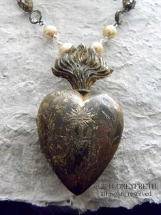 """The antique Ex Voto of the Sacred Heart was found in France. Beautifully engraved on the front is a graceful letter """"M"""" for """"Marie"""", a cross, and sinuous foliage. The piece is quite old and time and the elements have left their mark by way of a stunning patina in variegated hues. It appears almost as though this piece was buried deep in the earth with its secrets, and then rediscovered."""
