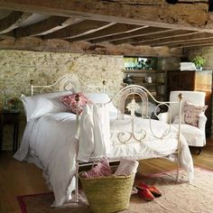 Farmhouse bedroom.  I love the wood beamed ceiling and the stone wall.