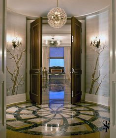 A tan and gold foyer decorated with large wooden double doors, a crystal chandelier with gold accents and an elegant floral wall motif. Interior Design Process, Luxury Interior Design, Interior Architecture, Vestibule, Wooden Double Doors, Chicago Apartment, Art Deco Buildings, Foyer Decorating, Decorating Blogs