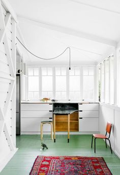 How fresh does a green floor look in this bright, white-walled space?