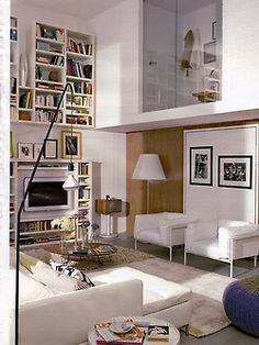 smart Italian home: behind the chairs is hidden bed. my fave are wall mounted bookshelves