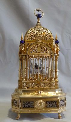Exceptionally rare silver gilt and enamel singing bird cage of delicate size and of very fine quality. The eight sided cage with canted corners sits on four paw feet and the base is decorated with inlaid blue enamel in a floral design. To the centre of the four main sides of the base a silver medallion shows two cupids fighting. The base is further decorated with florets, floral corner mounts and cherub heads. The cage itself is held up by eight decorative columns with acanthus decoration…