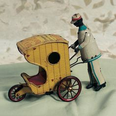 German Tin Wind-Up Mechanical Rollo-Chair. tin three-wheeled carriage simulating porter-driven wicker beach cars of early 20th century Atlantic City. c.1920