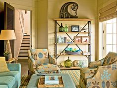 Tropical Living Area ~ Bottles and balls in shades of blue and green look like they just washed up on the shore in this South Carolina beachside living room. Modern lines and large-scale patterns make these armchairs the showpieces of the room.