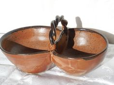 Double bowls with a handle glazed with continental clay nutmeg over black.