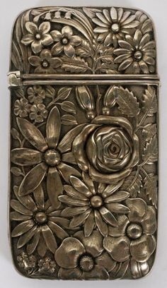 """FRANK M. WHITING & CO. REPOUSSE STERLING MATCH SAFE, C. 1900, H 2 1/2"""", W 1 1/2"""":Having a repousse floral motif, hinged cover, and match strike at the underside. Stamped with trademark logo along with """"Sterling"""". Weighs approximately 0.86 trz."""