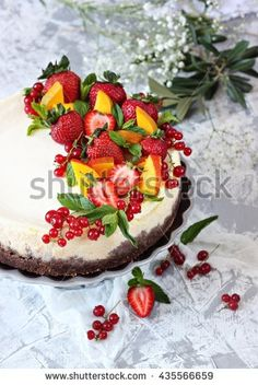 Cheese cake with chocolate biscuit and mango cream with strawberry , currant , mango and mint