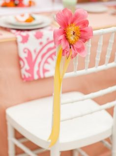 Add a special touch to your party chairs: simple silk flower tied with ribbon
