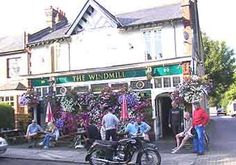 The Windmill, (or 'The Windy' as it is affectionately known) is a cosy little pub located in the bustling village of Hampton Hill on Windmill Road and opposite the Longford River. Finbar Burke has been efficiently running this friendly local for over a decade now and it has a good reputation for it's beers and a convivial comfortable atmosphere.    Parking is not a problem and it also has a large garden to the rear and front of pub seating beneath the abundant baskets