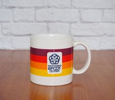 15 Disneys EPCOT Center theme park the first year it opened - 1982 (today its known simply as EPCOT). This souvenir mug features a wrap-around rainbow design in maroon, red, orange and yellow on white with the Epcot logo in the center on both sides. I love the bright cheery colors and retro styling of this 80s relic! The bottom is marked: Made Exclusively for Epcot Center © 1982 Disney JAPAN. It even retains the original price tag – $3.50 back in the day. You ...