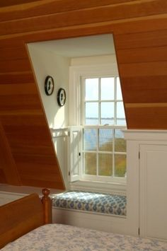Making the most of the attic space with a lovely window seat. I like the storage running along the roof line. Lift up the window seat for more storage.