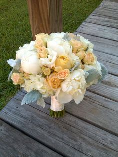 Bridal bouquet of peach garden and spray roses, white peonies, hydrangea and lisianthus with dusty miller foliage.