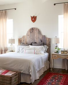 "Composed of red oak, the dramatic shape of the ""Duchess"" bed  (that headboard!) creates the perfect rustic-meets-refined effect. This cabin's bedroom gas a shabby chic look that we cannot get enough of."
