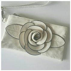 Cream/off white wristlet with flower FINAL PRICE Big flower on front of this adorable wristlet makes a super addition to any outfit!  Keep it in your handbag for essentials when you just need to run in the store!  Has zippered top and attached key fob.  New without tags. Boutique  Bags Clutches & Wristlets