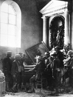 A squad of US soldiers listening to one of their comrades playing an organ in a  half-wrecked church during WWI. Photograph by J. A. Marshall. Exermont, Argonne, France, October 1918.