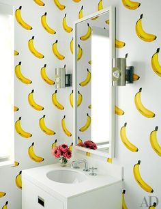 An animated bathroom featuring a banana-print wall cover by Flavor Paper…