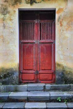 Old Vietnamese door and weathered yellow wall  Shot at Tu Duc tomb near Hue, Vietnam  Stock Photo