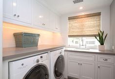 """Laundry Room. Laundry with white cabinets and gray walls painted in Benjamin Moore 1599 Marina Gray. Laundry room features Sleek Concrete #4003 Quartz countertop and 4"""" x 16"""" white subway tile as backsplash. #BenjaminMoore1599MarinaGray #BenjaminMoore #1599 #MarinaGray #BenjaminMoorePaintcolors Patterson Custom Homes"""