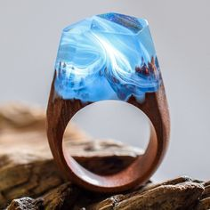 Each one of these rings are unique, using materials like flowers, gold flakes and ink coloring encased in resin to create a mysterious little diorama on your finger.