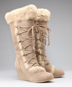 Trips to the mountain call for a super stylish wedge boot that fits right in with the winter wonderland. Before you make the trek from the slopes back to your warm log cabin, change out your ski boots and slip into this luxurious sheepskin-lined pair guaranteed to keep your tootsies toasty. Laced up with style and a pop of fur, you'll fall feet first in love with this savvy set.  •14'' calf circumference•14'' shaft•2.75'' heel•Suede upper•Wool lining