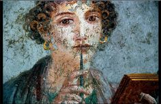 Roman paintings in ancient Pompeii.  The so-called Sappho girl.  This famous miniature, discovered in June 1760, has remained one of the most famous female portraits from Pompeii. It has the air of gracious refinement that surrounds this girl, caught in a moment of meditation before putting pen to paper.  Archaeological Museum, Naples, Italy