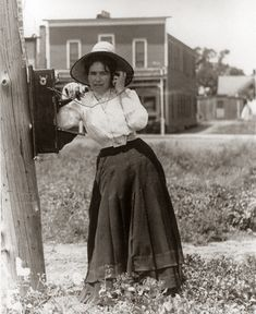 1900, Woman Talking On Hand Crank Oak Telephone. Job description: that would be early Girl Friday.  She's checking with the boss to see what else he needs to be done.