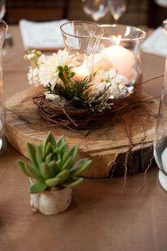 A decorating trend we are seeing more and more.  Like this woodsy centerpiece with succulents.  Christmas rustic theme party.