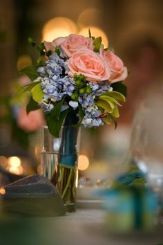 Blue hydrangeas with green hypericum berries, green orchids, and peach roses