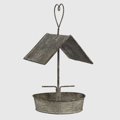 """$22.00 Add some farmhouse fun to your yard with our Slanted Roof Bird Feeder and Heart Hanger! Your feathered friends will flock to this metal feeder, with its slanted roof, 2 bird posts and a heart-shaped metal hanger. This bird feeder is so wonderful that you might want to hang it inside and enjoy its rustic charm up close.   Made of metal. Dimensions: 7"""" x 7"""" x 13.5"""" H."""