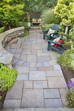 The side garden used to be a grassy slope, worn ragged by a Slip'N Slide and dog play. Designer Phil Wood used stone for paving, walls and seating to define an outdoor room for entertaining and gathering.