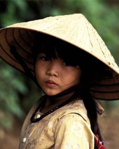 Vietnamese girl in ao dai and a nón lá (leaf hat). This ensemble is associated with the central city of Huế, Vietnam.