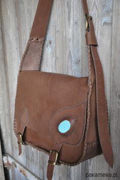 Ręcznie wykonana  torba ze skóry  naturalnej w  kształcie teczki , w  kolorze   brązowym.Zszywana  rzemieniami.Ozdobiona otoczakiem  turkusu obszytym  naturalnym sznurkiem  .Zamykana na klamry  - 3 cm. Torba ma   wewnętrzną   kieszonkę zamykaną  na zamek.Szerokość  torebki-36 cm  ,wysokoś...
