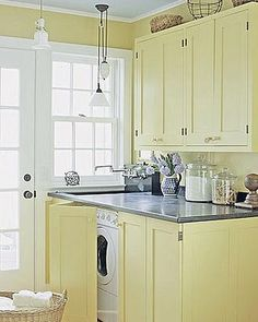 Front Loading Washer and Dryer - bi-fold doors, wall cabinets and a coordinating countertop all work together to hide these necessary appliances - via A Perfect Gray