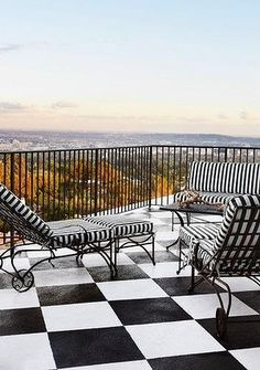 A monochrome patio offers serene views over treetops.