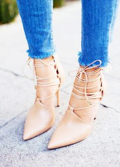 Nude pointed-toe lace-up heels.
