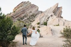 Vasquez rocks wedding photo shoot bride lace style gown with high neckline and red and orange rose floral headpiece with groom grey suit with white dress shirt and tan stripped bow tie with rose boutonniere