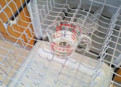 Place a dishwasher-safe cup filled with plain white vinegar on the top rack of the dishwasher. Using the hottest water available, run the dishwasher through a cycle. The vinegar will help to wash away the loose, greasy grime, sanitizes, and helps remove the musty odor.  Next, sprinkle a cupful of baking soda around the bottom of the tub and run it through a short  cycle. The baking soda will help freshen and removing stains.