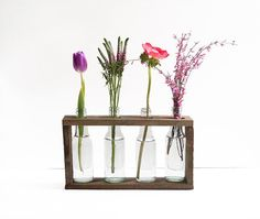 Turn small glass bottles into into a charmingly rustic grouped vase for your favorite flowers with this wooden bottle vase holder tutorial!