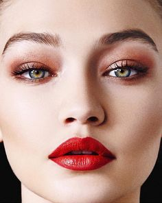 Blushed nudes eyeshadow and a bold orange lip make Gigi Hadid's face irresistible.