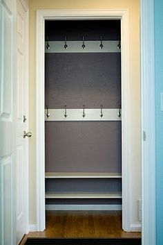 "entry closet turned mudroom - with one long row of hook placed 3/4 way up the wall, shelf above with baskets, bench seating with shoe storage below and a ""SKWIRA"" photo art sign in the middle"