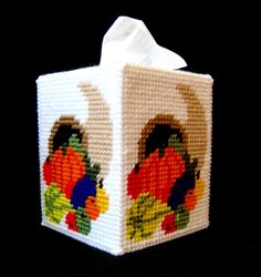 Convey the feeling of Thanksgiving with this tissue box cover Made from 7-mesh plastic canvas and 4-ply yarn, this cover will fit a 4 1/2 (11.43 cm) square box of tissues and is 5 3/4 (14.61 cm) high. Tissue box cover is worked in a white tent stitch background with a cornucopia worked