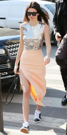 Reality star-turned-model Kendall Jenner hit the streets of Paris in a glam high-shine mirrored crop top and a pretty peach high-slit skirt that she expertly grounded with a cool pair of black-and-white low-tops.