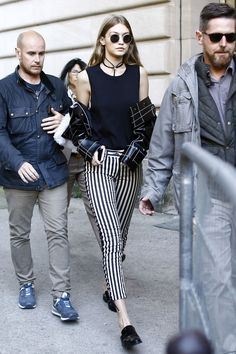 October 3, 2016 / Wearing a black tank top, lace-up striped pants, mule loafers, an embroidered leather jacket, rounded sunglasses and a choker while leaving the Giambattista Valli show in Paris.