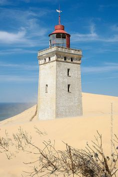 Europe | Rubjerg Knude Lighthouse, Denmark. 75 feet tall, built in 1900 on a dune-less cliff 656 ft from the sea and 200 ft above sea level. Elements have slowly swallowed it over the years. Abandoned in 1968.