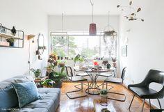 Sala de jantar tem mesa redonda e suportes para plantas no chão.